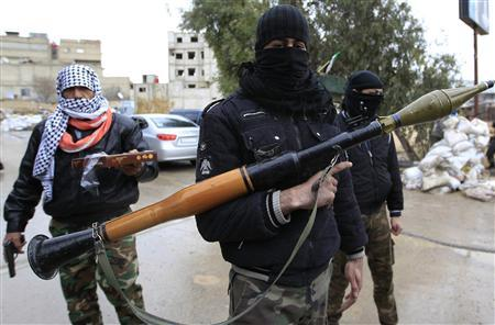 Syrian soldiers, who have defected to join the Free Syrian Army, look on as one holds up an RPG and another (L) delivers sweets in Saqba, in Damascus suburbs, January 27, 2012.  REUTERS/Ahmed Jadallah