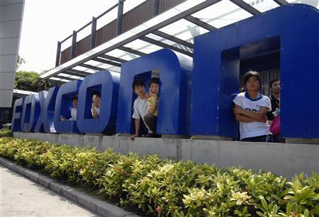 Workers stand at the gate of a Foxconn factory in the township of Longhua in Shenzhen, Guangdong province in this May 26, 2010 file photo. REUTERS/Stringer