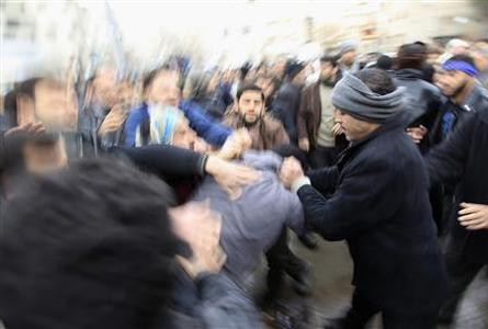 A pro-Assad policeman is beaten by protesters during the funeral of Mazen abou Dhahab, who was killed in a protest in Saqba, Damascus suburbs, January 27, 2012. REUTERS/ Ahmed Jadallah
