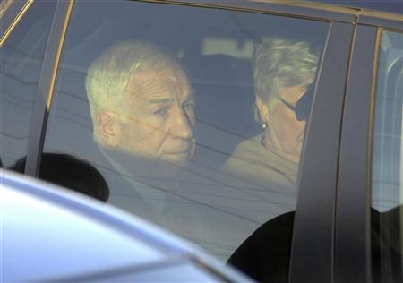 Former Penn State assistant football coach Jerry Sandusky (L) sits in his car with his wife Dottie after departing from a preliminary hearing to determine if there is enough evidence to hold him for trial on charges of sexually abusing boys, at the Centre County Courthouse in Bellefonte, Pennsylvania, December 13, 2011.    REUTERS/Pat Little