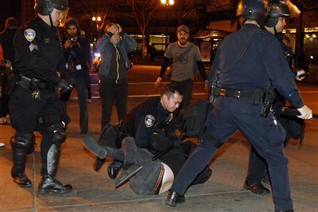 A group of police officers from various law enforcement agencies arrest an Occupy Oakland demonstrator near Frank H. Ogawa Plaza during a day-long protest in Oakland, California January 28, 2012.    REUTERS-Stephen Lam