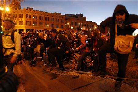 Occupy Oakland demonstrators run over a fence in an attempt to escape from the police encirclement during a day-long protest in Oakland, California January 28, 2012.      REUTERS-Stephen Lam