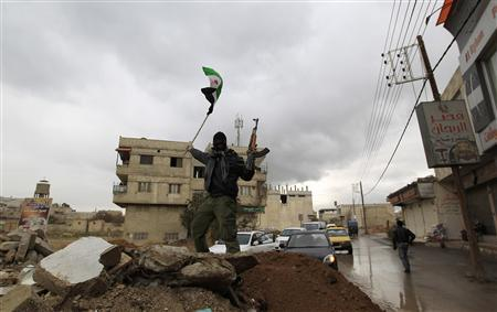 A Syrian soldier, who has defected to join the Free Syrian Army, holds up his rifle and waves a Syrian independence flag in the Damascus suburb of Saqba January 27, 2012.  REUTERS-Ahmed Jadallah