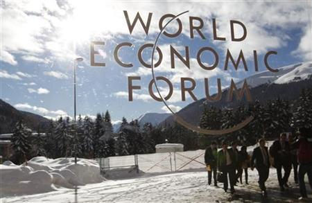 Visitors are reflected in window of the congress center, venue of the World Economic Forum (WEF) in Davos, January 26, 2012. REUTERS/Arnd Wiegmann