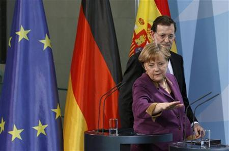 German Chancellor Angela Merkel gestures next to Spain's Prime Minister Mariano Rajoy as they arrive for a news conference after a meeting in Berlin January 26, 2012. REUTERS/Tobias Schwarz