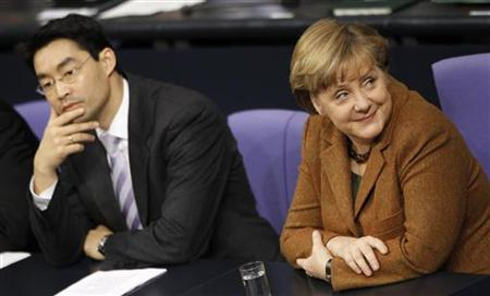 German Economy Minister Philipp Roesler (L) and Chancellor Angela Merkel attend a session of the lower house of parliament Bundestag in Berlin, January 19, 2012.     REUTERS/Fabrizio Bensch