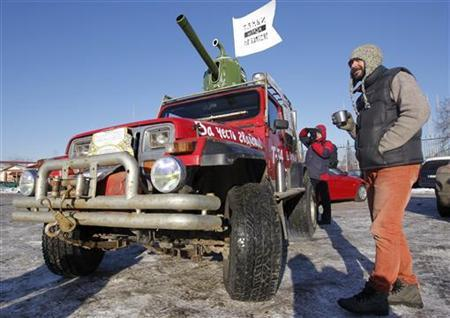 A participant stands near his car, which was modified to resemble a tank, before taking part in ''The White Ring'', a protest motor rally in Moscow January 29, 2012. REUTERS/Anton Golubev