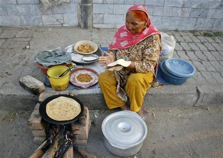 Rani Bibi, 76, prepares ''roti'' (bread) along a roadside in Faisalabad, located in Pakistan's Punjab province, October 6, 2011. Bibi earns about 400 Pakistan Rupees ($ 4.60) a day. REUTERS/Fayyaz Hussain