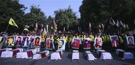 Tibetan exiles holding portraits of Tibetan protesters whom they said were killed during demonstrations in China's Sichuan province, stand behind mock coffins during a protest in New Delhi January 29, 2012. REUTERS/Parivartan Sharma