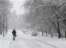 Человек идет по заснеженной улице в Киеве 22 января 2012 года. Сильные морозы, пришедшие на Украину на минувшей неделе, привели к смерти 12 человек и госпитализации 285, сообщило Министерство по чрезвычайным ситуациям. REUTERS/Gleb Garanich