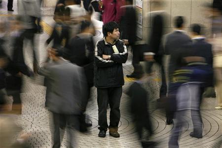 People walk past a man outside Shinjuku train station in Tokyo May 16, 2008.   REUTERS/Kiyoshi Ota