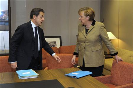 France's President Nicolas Sarkozy and Germany's Chancellor Angela Merkel wait for Italy's Prime Minister Mario Monti (not in picture) prior to a meeting at the European Council in Brussels ahead of the European Union leaders summit January 30, 2012.  REUTERS/Philippe Wojazer