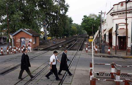 Mormon missionaries or elders Owens, Valente and Velez (L-R) cross a railroad as they mission in San Fernando, on the outskirts of Buenos Aires, February 17, 2009. REUTERS/Marcos Brindicci