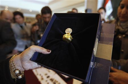 An employee displays a recovered tiny gold jar, dating to 4,500 BC at the Iraqi Ministry of Foreign Affairs headquarters in Baghdad January 30, 2012.     REUTERS-Saad Shalash