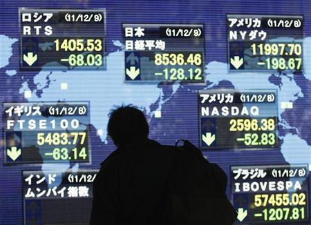 A man looks at an electronic board displaying a fall in major market indices around the world outside a brokerage in Tokyo December 9, 2011. REUTERS/Issei Kato