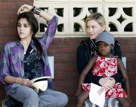 U.S. pop star Madonna looks at her daughter Lourdes (L) as she holds her adopted Malawian child Mercy James during a visit to Gumulira village, about 80 km (50 miles) from the Malawian capital Lilongwe, April 5, 2010. REUTERS/Mike Hutchings/Files