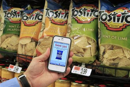 A customer with the Scan It! Mobile app on his iPhone shows a coupon for Tostitos chips while shopping at Stop and Shop supermarket in Braintree, Massachusetts October 17, 2011. Retailers are in the midst of the technology revolution. REUTERS/Adam Hunger