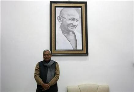 Bihar's chief minister and leader of Janata Dal United party Nitish Kumar poses in front of a portrait of Mahatma Gandhi after an interview with Reuters in Patna, Bihar, January 9, 2012. REUTERS/Adnan Abidi