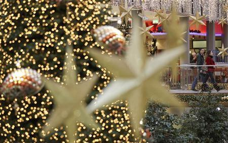 Shoppers walk among illuminated Christmas decorations in a shopping mall at Berlin's Potsdamer Platz December 24, 2010.  REUTERS/Fabrizio Bensch