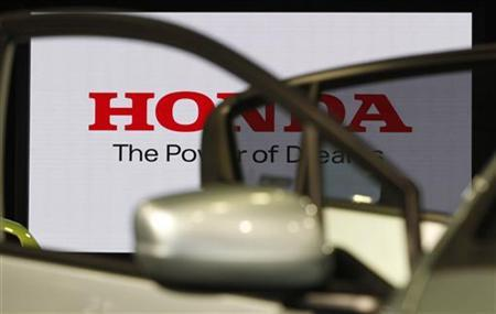 Logo of the Honda Motor is seen through car doors at the company showroom in Tokyo October 31, 2011. REUTERS/Issei Kato/Files