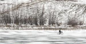 Мужчина едет на велосипеде по руслу замерзшей реки Днестр у села Жванец 15 января 2008 года. Сильные морозы, пришедшие на Украину на минувшей неделе, привели к смерти 30 человек и госпитализации 544, сообщило Министерство по чрезвычайным ситуациям. REUTERS/Konstantin Chernichkin