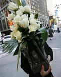 <p>A delivery man carries a bouquet of white roses for delivery on Valentine's Day in New York City February 14, 2008. REUTERS/Mike Segar</p>