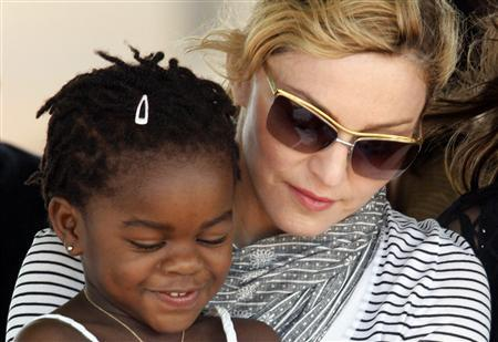 Pop star Madonna sits with her adopted Malawian child Mercy James during a bricklaying ceremony at the site of her Raising Malawi Girls Academy, near the capital Lilongwe in this April 6, 2010 file photo.    REUTERS/Mike Hutchings/Files