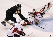 """Нападающий """"Бостона"""" Милан Лучич (вверху слева) бросает по воротам """"Оттавы"""" в матче НХЛ в Бостоне 31 января 2012 года. """"Бостон"""" одержал домашнюю победу над """"Оттавой"""" со счетом 4-3 в матче регулярного чемпионата НХЛ, отыграв по ходу встречи разницу в две шайбы. REUTERS/Jessica Rinaldi"""