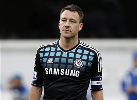John Terry of Chelsea looks over at the Queens Park Rangers fans as they chant insults at him during an injury break in their FA Cup soccer match at Loftus Road in London, January 28, 2012.  REUTERS/Andrew Winning