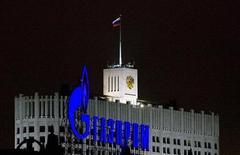 """Логотип Газпрома на фоне здания Белого дома в Москве, 14 января 2009 г. Российский Газпром """"в ближайшее время"""" ждет """"обновленных"""" предложений от Китая по цене на газ из РФ и не увеличивает долю спота в контрактах с европейскими потребителями, заверили в среду представители газового концерна. REUTERS/Sergei Karpukhin"""