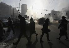 Люди переходят дорогу в Киеве 1 февраля 2012 года. Замерзающая Украина прекратила экспорт электроэнергии в Белоруссию из-за холодов и начинает закупки у России, чтобы закрыть возникший дефицит. REUTERS/Anatolii Stepanov
