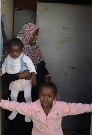 Rabha Mouftah, 38, walks with two of her four children at the displaced persons camp in Benghazi October 15, 2011. Mouftah says she had to flee Tawergha with her children after a vengeful mob stormed into her town last summer. After weeks on the run, thousands of black Libyans driven from their homes during the revolt against Muammar Gaddafi have resurfaced across the country, finding refuge in a squalid camp they hope is only temporary. REUTERS/Brian Rohan