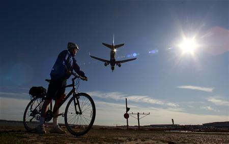 A cyclist out enjoying unseasonably warm temperatures watches a plane land at Ronald Reagan Washington National Airport January 31, 2012. REUTERS/Kevin Lamarque