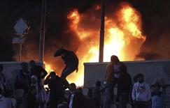 Um torcedor corre de um incêndio num estádio no Cairo, no Egito, nesta quarta-feira. 01/02/2012 REUTERS/Stringer