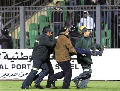 Medical personnel carry a wounded soccer fan at Port Said Stadium February 1, 2012.  REUTERS/Stringer