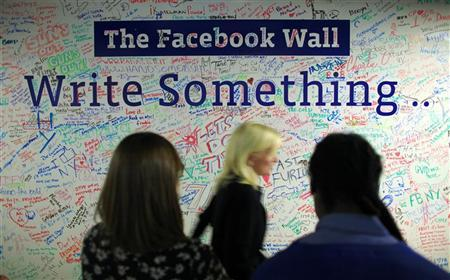 People walk past the Facebook wall inside their office in New York December 2, 2011.  REUTERS/Eduardo Munoz