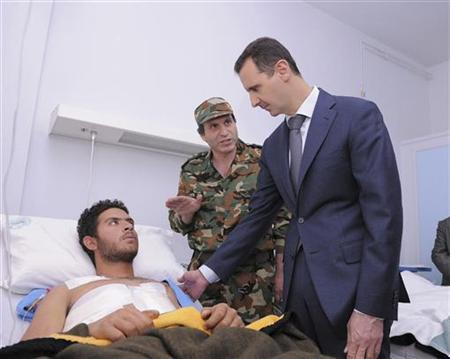 Syria's President Bashar al-Assad (R) during his visit to wounded troops who injured in clashes with rebels against his regime, at Youssef al-Azmaha military hospital, in Damascus January 31, 2012, in this handout photograph released by Syria's national news agency SANA. REUTERS/SANA Handout