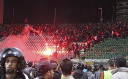 Футбольные болельщики покидают стадион в египетском городе Порт-Саид, 1 февраля 2012 года. Как минимум 74 человека погибли в результате столкновения футбольных фанатов и давки на матче в египетском городе Порт-Саид, дав повод и болельщикам, и политикам обвинить в случившемся правящих в стране военных. REUTERS/Stringer