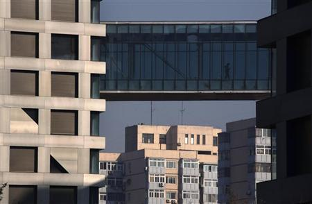 A man walks across a pedestrian bridge joining two residential apartment buildings in central Beijing January 12, 2012.  REUTERS/David Gray