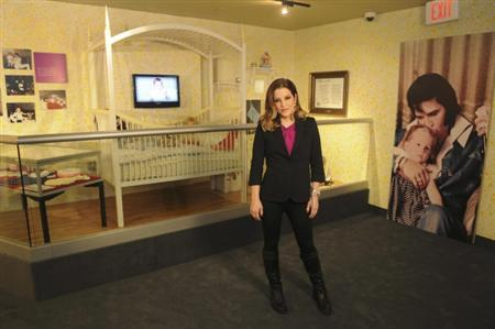 Elvis Presley's daughter, Lisa Marie Presley, poses with her new exhibit at Graceland the Memphis, Tennessee estate in this handout released on February 1, 2012. REUTERS/Handout