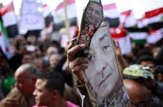 Um manifestante segura sapato com fotos do Marechal Mohamed Hussein Tantawi e membros do velho regime durante um protesto que exige que o Exército transfira o poder para civis, na Praça Tahrir, no Cairo. 27/01/2012  REUTERS/Suhaib Salem