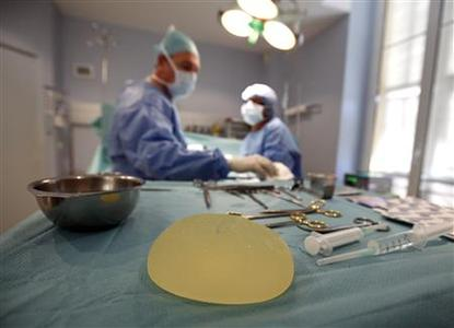 A defective silicone gel breast implant manufactured by French company Poly Implant Prothese (PIP) is seen near surgical instruments after being removed from a patient by plastic surgeon Denis Boucq (L) in a clinic in Nice December 21, 2011.   REUTERS/Eric Gaillard