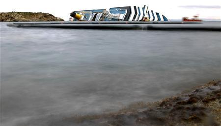 Oil barriers are seen next the Costa Concordia cruise ship that ran aground off the west coast of Italy, at Giglio island February 2, 2012. REUTERS/ Max Rossi