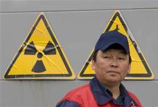 """Рабочий на фоне знаков радиационной опасности на урановой шахте в южном Казахстане 24 апреля 2009. Казахстан не будет наращивать урановую добычу в этом году, сообщил в четверг правительственный чиновник, отметивший вялый спрос на рынке, объятом """"фобиями"""" после прошлогодней аварии на японской АЭС в Фукусиме. REUTERS/Shamil Zhumatov"""