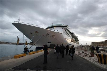People walk towards the Royal Caribbean cruise liner ''Brilliance of the Seas'' in Valletta's Grand Harbour December 14, 2010. REUTERS/Darrin Zammit Lupi/Files