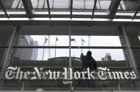 A window washer cleans the windows above the front door of the New York Times building in New York, March 26, 2010.   REUTERS/Gary Hershorn