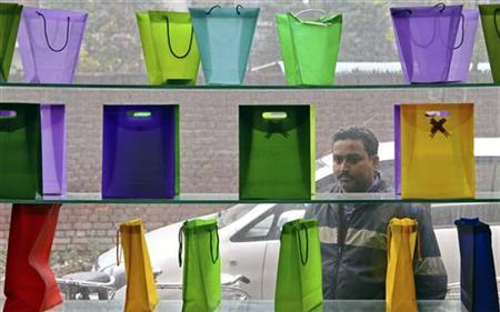 A man looks at poly-bags on display outside a factory at Ludhiana in the northern Indian state of Punjab January 18, 2012.    REUTERS/Ajay Verma