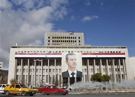 A picture of Syria's President Bashar al-Assad is seen on a central bank building in Damascus January 23, 2012.    REUTERS/Khaled al-Hariri