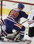 """Форвард """"Эдмонтона"""" Сэм Ганье (в центре) забивает четвертую шайбу в ворота """"Чикаго"""" в домашнем матче, 2 февраля 2011 года. Форвард """"Эдмонтона"""" Сэм Ганье набрал в четверг восемь очков в матче против """"Чикаго"""" и стал 11-м игроком в истории НХЛ, которому удалось в одной игре показать такую результативность. REUTERS/Dan Riedlhuber"""
