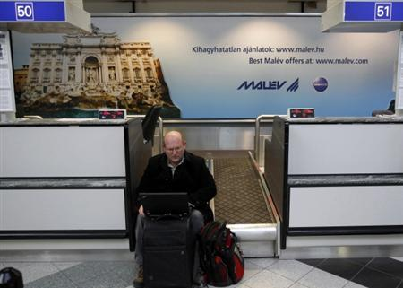 A man uses his laptop as he waits at Ferenc Liszt airport in Budapest February 3, 2012.  REUTERS/Laszlo Balogh